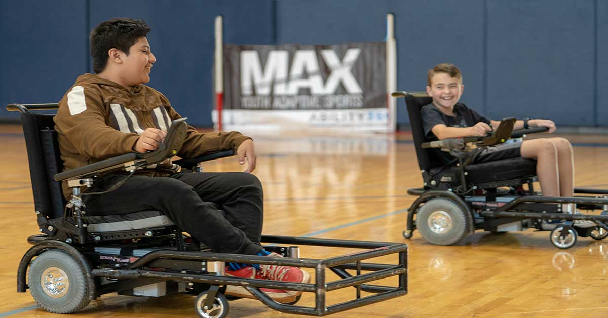 Two young boys playing power wheelchair soccer in Ability360's Sports & Fitness Center. One boy, wearing a brown and white jacket, black jeans and faded red vans, uses his power wheelchair to push the soccer ball towards another boy. The other boy wears a black t-shirt and black basketball shorts.