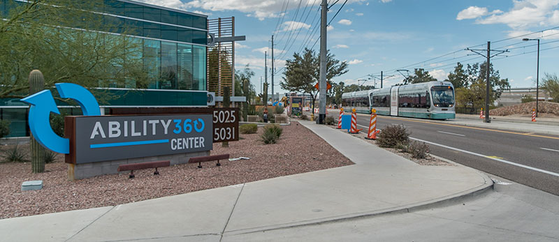 The main entrance of Ability360 featuring a large sign in front of the main offices showing Ability360's address. On the right, a light rail is shown passing through the intersection.