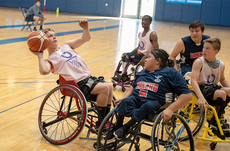 A blonde-haired teenager, wearing a white basketball tank top and black basketball shorts, is attempting to shoot a basketball over top of a dark-haired woman wearing a navy blue shirt and matching basketball shorts. The woman wears her hair in a ponytail and is holding the wheels of her wheelchair.