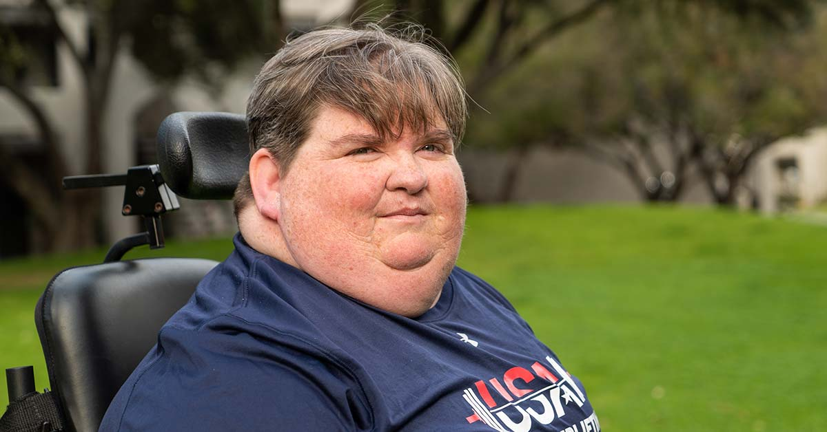 A middle-aged woman with short gray hair sits in a power wheelchair and smiles at the camera. Her navy blue shirt says USA Para powerlifting.