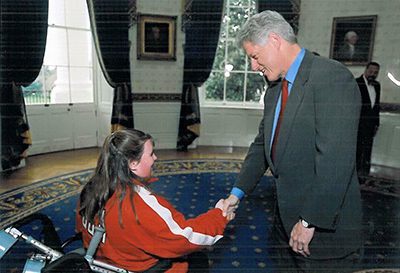 Mary Stack, wearing a red jacket with a large white stripe down both arms shakes the hand of former President Bill Clinton. President wears a charcoal gray suite with a sky blue button down and a red tie in the Oval Office.