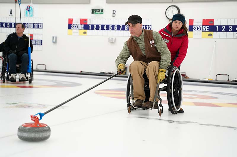 A man wearing a black baseball cap, a white and green checkered button up, a brown vest, yellow gloves, khakis and brown boots sits in a manual wheelchair pushing a curling stone towards the target.