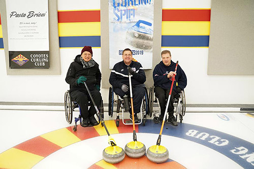 Three men sit in their manual wheelchairs smiling at the camera with their curling stones in front of them. The man on the far left is wearing black sneakers, black cargo pants, a black hoodie, a black and white scarf is wrapped around his neck, turquoise gloves and a maroon beanie. The man in the middle wears black sneakers, black pants, a black pullover, grey gloves and wears thin-framed glasses. The man on the far right is wearing black sneakers, black cargo pants, and a navy blue hoodie.