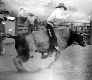 Photo of a person riding a bull