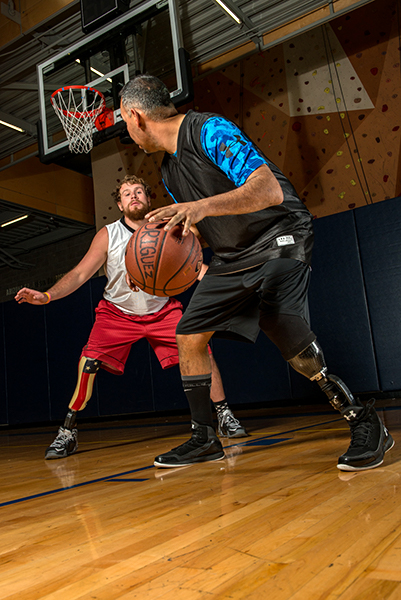 Two men who have amputations face off in a basketball game.