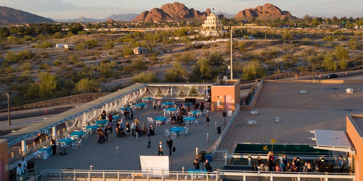 Ariel view of the Ability360 Center rooftop. People are meeting on the roof and using dressed tables at the event. There is a beautiful desert view with mountains in the background.