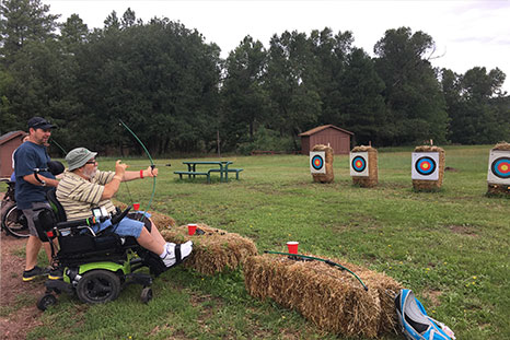 A man in a wheelchair prepares to shoot an arrow at a target on an archer field.
