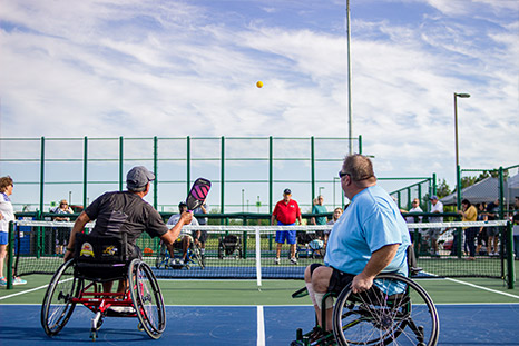 Two men in wheelchairs play pickleball.