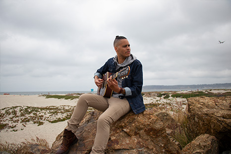 James Ian sits on a rock at the beach, posing with his guitar in a playing position.
