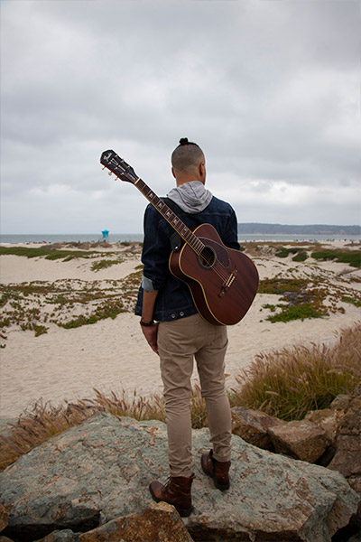 James Ian stands on a rock at the beach with his guitar hanging on his shoulders by the guitar strap. His back is to the camera and he is looking out at the beach in front of him.