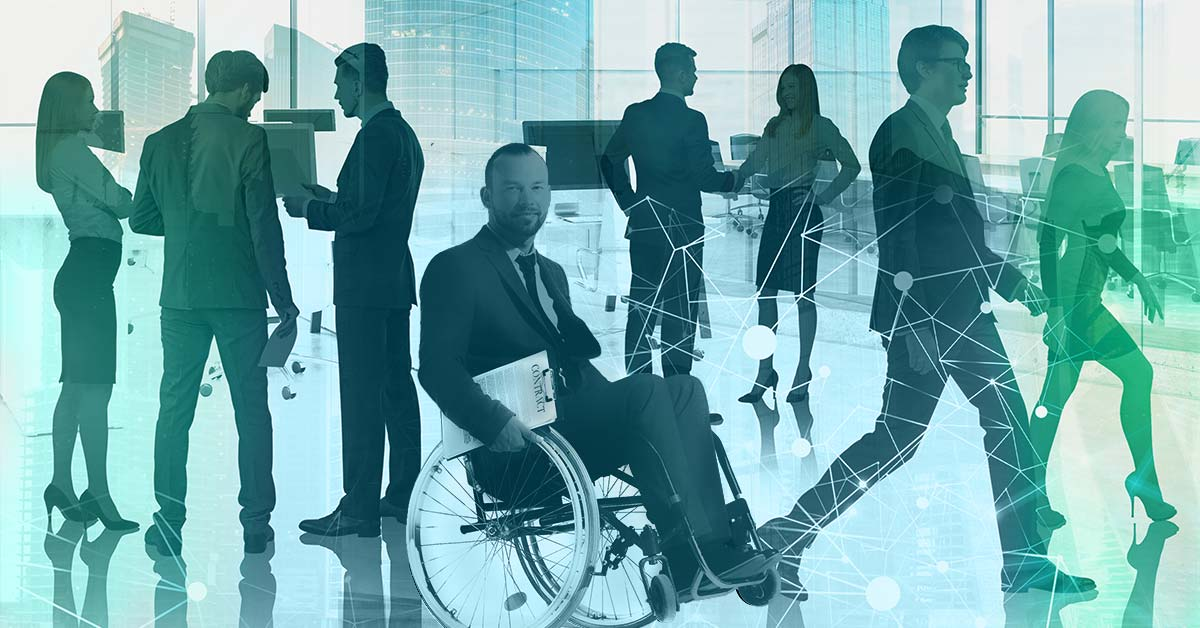 A man wearing a suit in his manual wheelchair does a wheelie while holding a clipboard, and is surrounded by other business-like looking people.