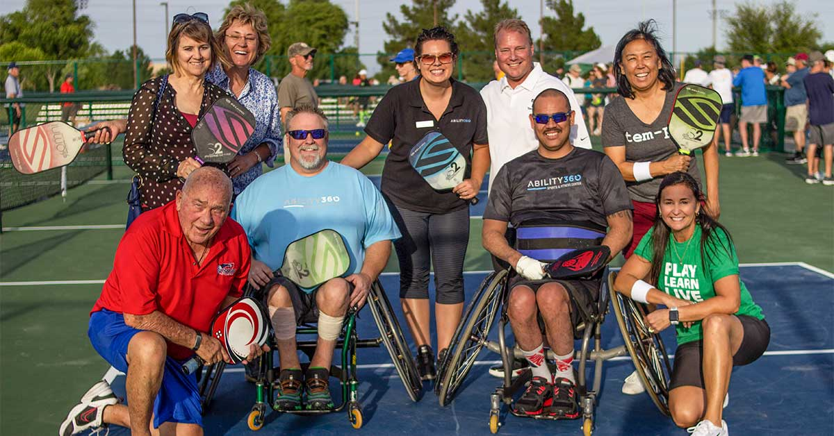 A group of people pose with the mayor of Tempe, all holding pickleball paddles and smiling at the camera.