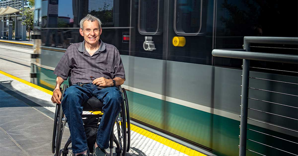 Ability360 President and CEO, Phil Pangrazio, sits in front of the new light rail station on 50th street and Washington outside of Ability360. A light rail passes behind him.