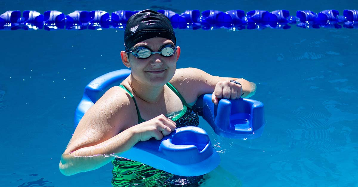 A woman in a green swim suit, black swim cap and goggles, balances using a device similar to a pool noodle but allows for the user to feel more comfortable. There are cup holders that double as hand-holds at the ends of the floatation device.