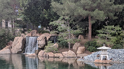 There are trees in the background. A waterfall pours from rocks just in front of the tree. A little house structure sits on some rocks in the middle of a lake.