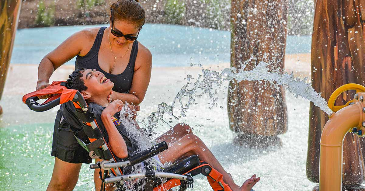 A young boy sits in his water-friendly manual wheelchair in front of a water feature at Morgan's Inspiration Island with his mom standing beside him laughing.