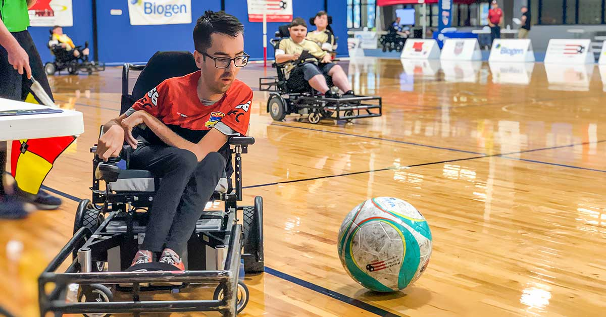 A young man in a wheelchair power soccer chair lines up to strike the ball at Nationals in Indiana. The man wears an orange Ability360 FC jersey.