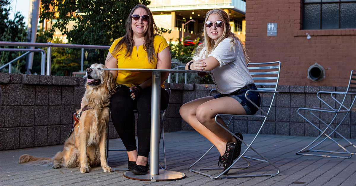 Rachel, wearing a yellow ASU shirt, sits at a table next to her daughter who is wearing a white shirt and sunglasses. Rachel's golden retriever guide dog, Austin, sits at Rachel's feet next to the table.