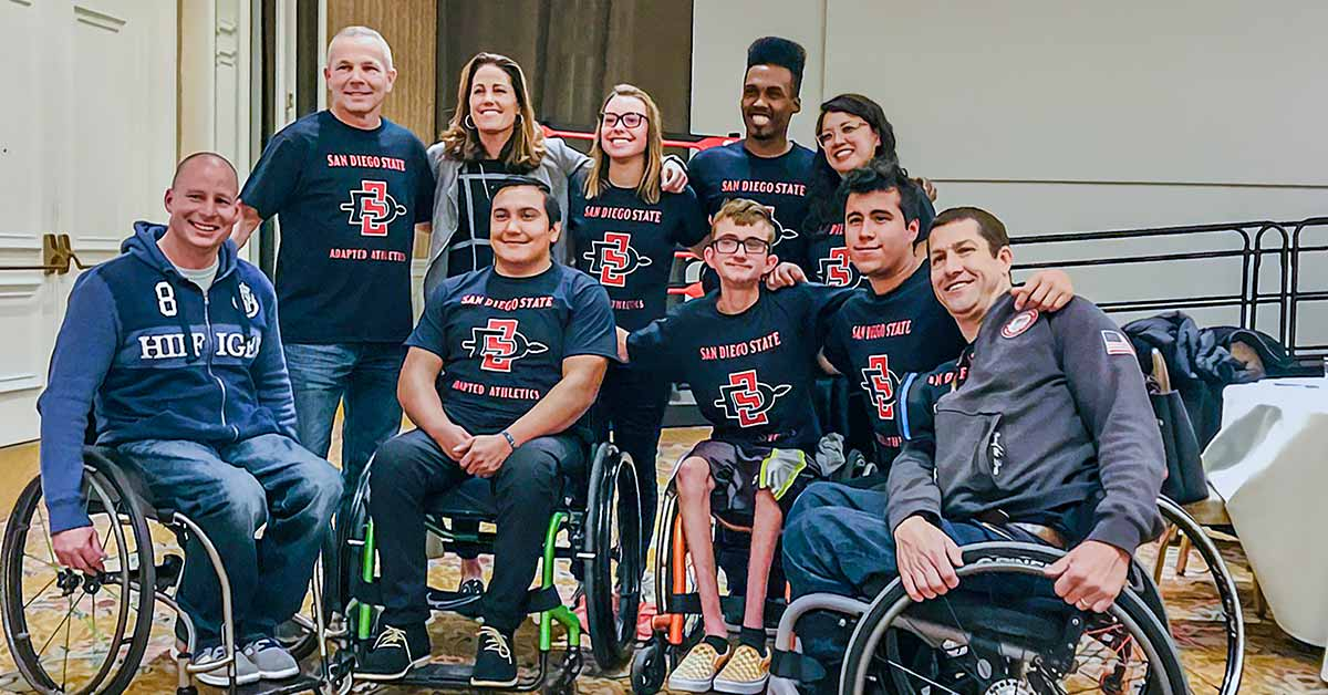 Five wheelchair athletes smile at the camera. Behind them stand five people in San Diego State University shirts with their arms around each other.