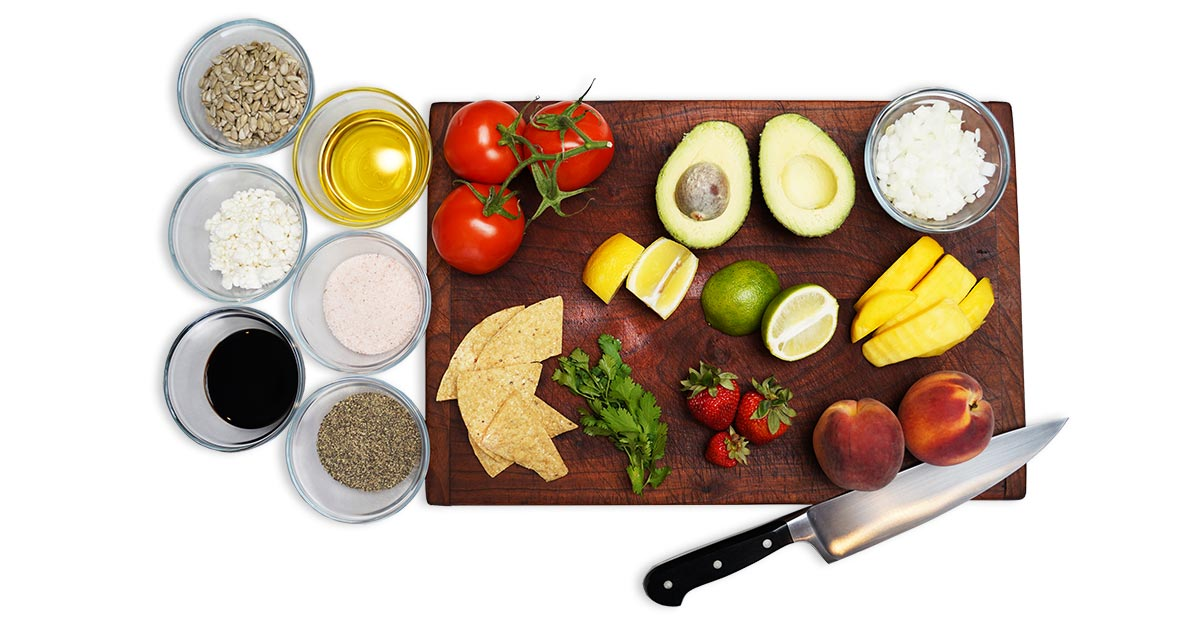A spread of different ingredients sitting on a cutting board and in glass bowls to the left of the board. On the board are mango slices, peaches, strawberries, tomatoes, lemon slices, lime slices, chips, avocado and cilantro. In the bowls are various seasonings.