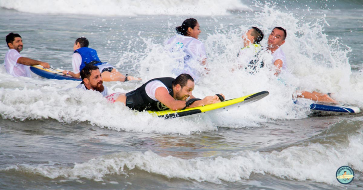 A picture of Three different surfers riding waves in chest-high water. All of the surfers are laying down on the surfboards, with a supervisor behind them for safety.