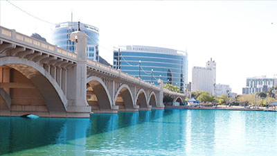 View of the Tempe Town Lake. The bridge crosses over the lake and building rise up behind the bridge.