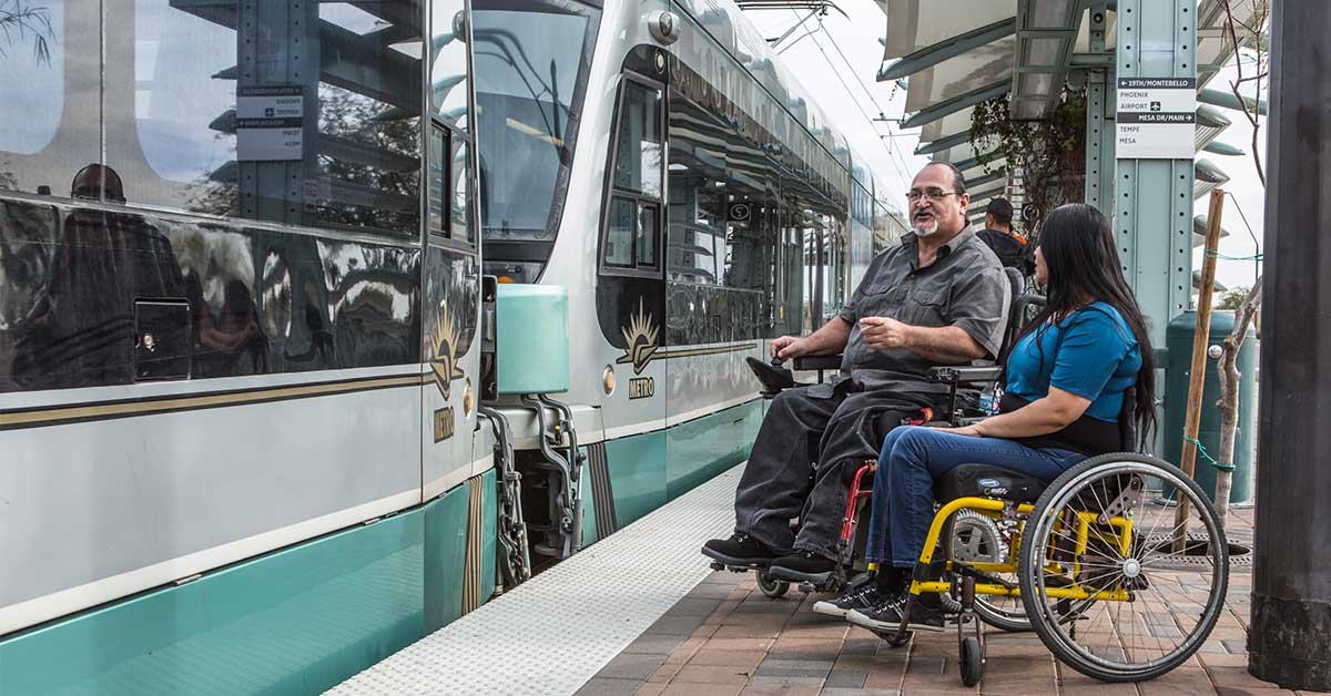 A man sits in a red power chair while talking to a woman sitting in a yellow manual wheelchair. The light rail is pulling up in front of them.