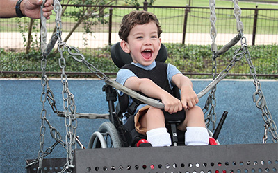 A child younger than seven sits in his wheelchair on a wheelchair-accessible swing with a smile on his face.