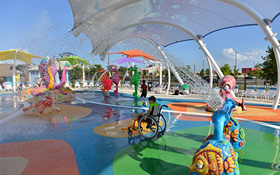A large, colorful splash pad with awnings protecting from the sun as a young boy in a manual wheelchair sits in the middle.