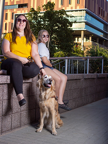 Rachel poses for a picture with her daughter, Madison. Rachel's guide dog, Austin, sits in front of them. Behind them is the downtown ASU campus.