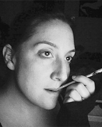 Black and white portrait of Rachel Fisher with the end of a paint brush in her mouth, contemplating her art.