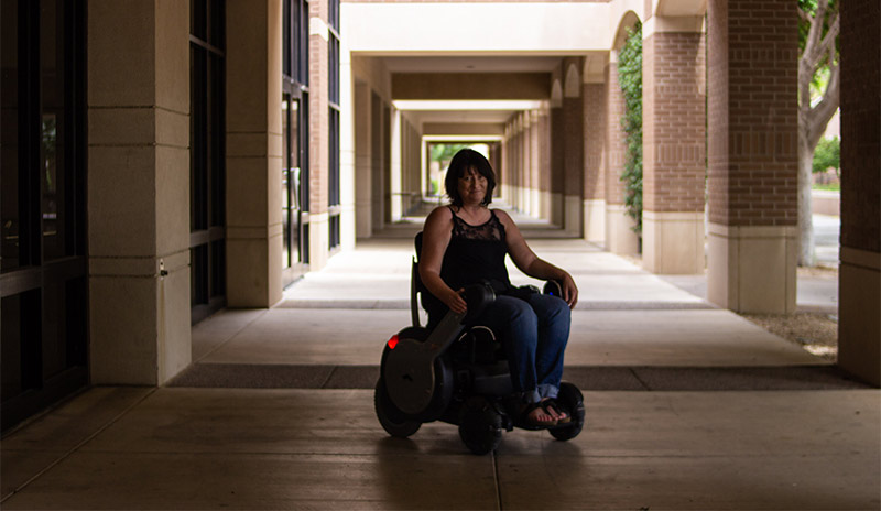 Theresa Devine, associate professor at ASU, poses for a picture in her power wheelchair in front of the lawn at ASU West.