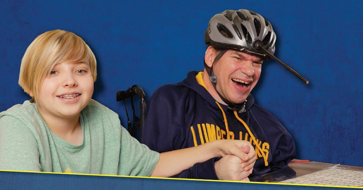 A blond child holds the hand of a smiling man who uses a wheelchair. He is wearing a helmet with a pointer.