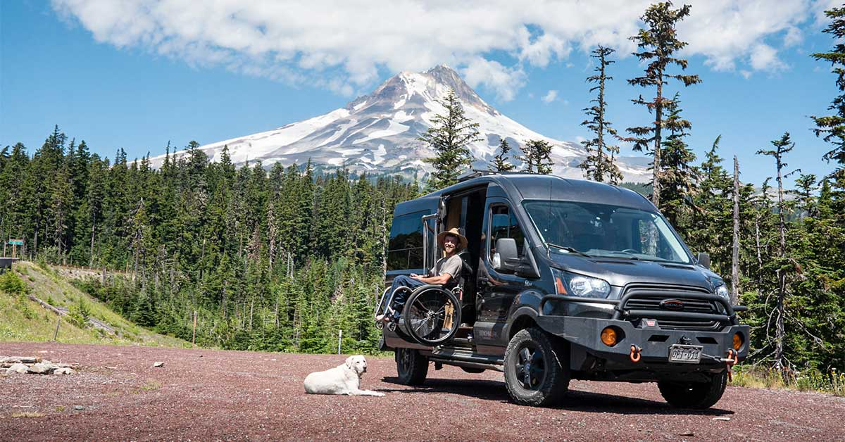 PHOTO: A scenic picture of a black transit van with a man in a wheelchair being lifted up into the van. On the ground in front of the man is a labrador retriever. The man wears blue jeans, a gray t-shirt and a beach hat. Behind the van is a forest and a snow-covered mountain behind him.