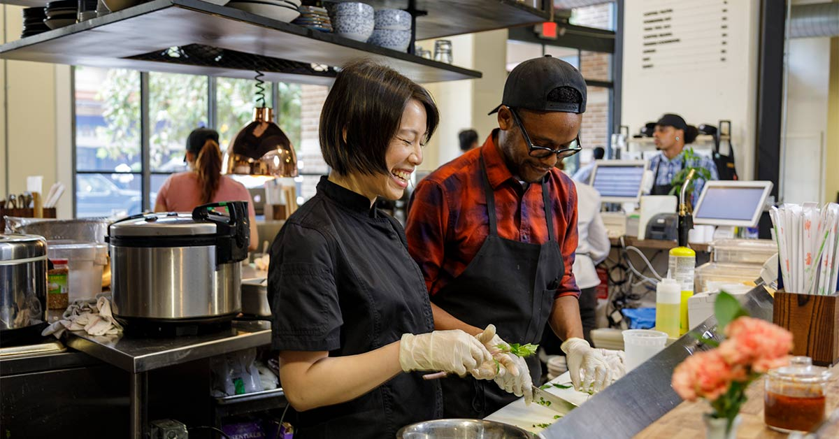 PHOTO: Christine Ha, wearing a black chef's coat and rubber gloves stands next to a man wearing a black backwards hat, thick rimmed glasses, a red and black checkered button up and a black apron. They stand side-by-side inside of a kitchen at The Blind Goat and are chopping vegetables.