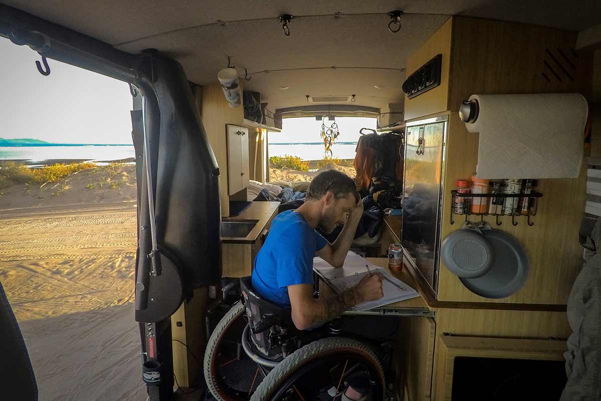 PHOTO: Kirk hangs out the side of his van on the wheelchair lift. He wears a red surf shirt, a tan hat, and is looking out towards a beach.