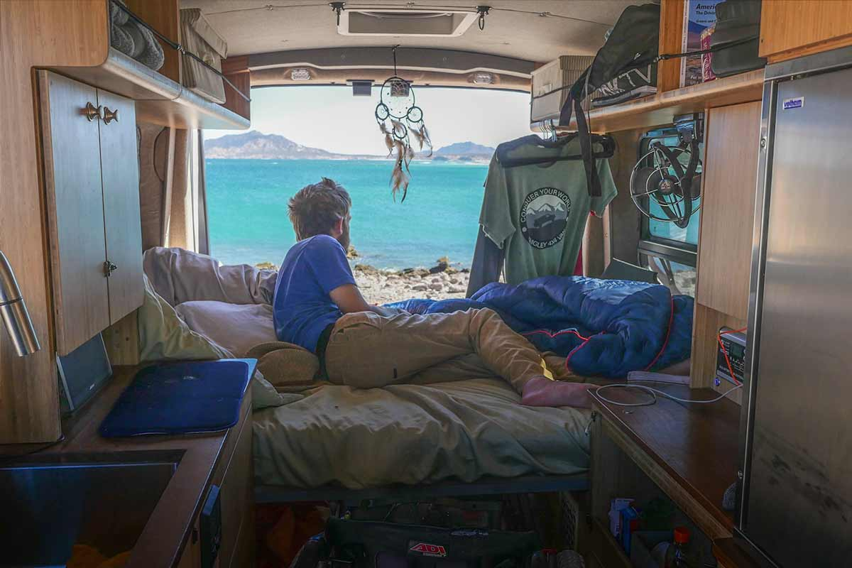 Photo: A photo of Kirk Williams laying on his bed inside his bed. He wears khaki pants and a blue shirt and is leaning out towards the back of the van. The back doors of the van are open and Williams is on a beach with an ocean in front of him.