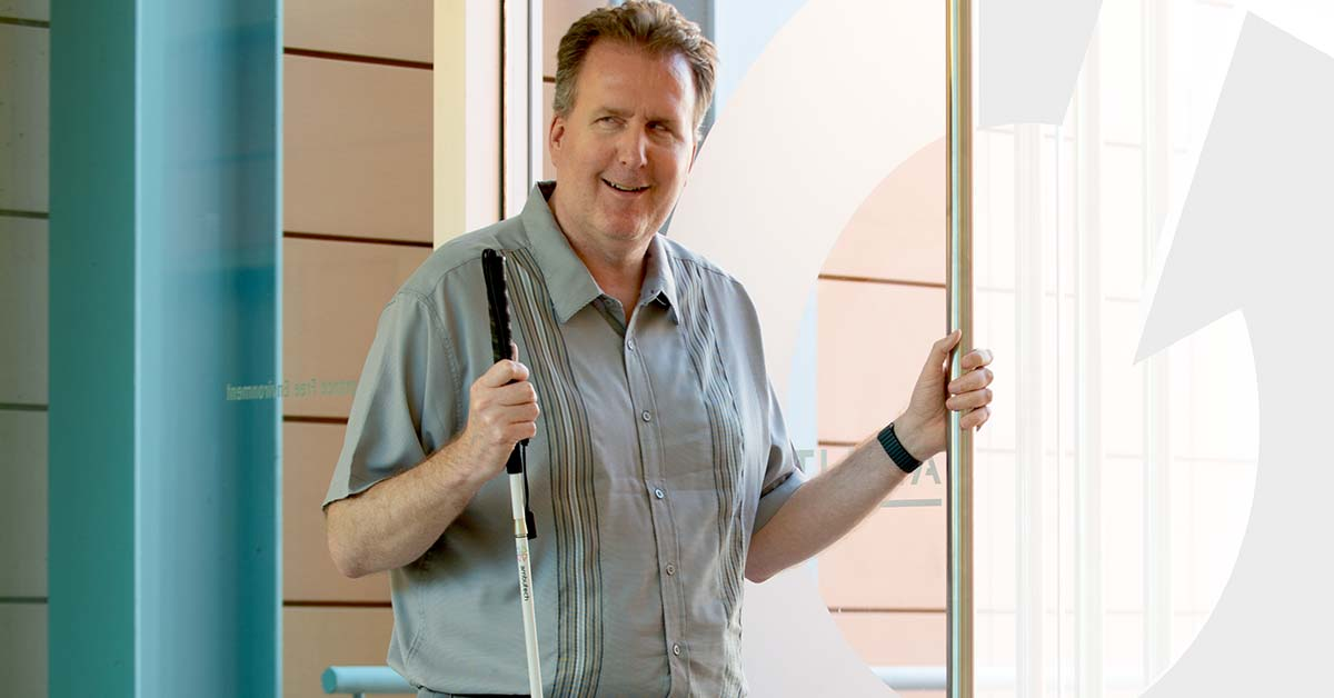 PHOTO: Larry Wanger, Ability360's Vice President of Employment Services stands by a glass door. His left hand is holding the door handle. In his other hand is his probing-white cane. He wears black shoes, gray pants, a greenish button down shirt with short sleeves and is smiling directly at the camera.