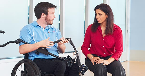 A picture shows two people, a man and a woman, looking down at an assistive gait training device. The woman, sitting on the right, wears a red button down shirt and black slacks. She wears her brown hair straight down and just past her collar bones. The man to the left, wears black jeans, and a baby blue polo shirt. He sits in a manual wheelchair and is holding up the device to show her.