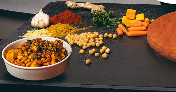 An overhead shot of an assortment of spices and vegetables on dark grey slate. The spices are in neat piles.