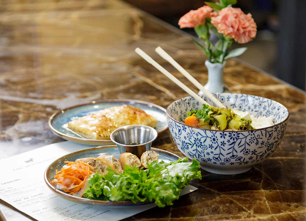 PHOTO: A full spread of Vietnamese food in white and blue glassware. One plate shows eggrolls cut in half, with a small tin cup of dip and lettuce. The next plate shows the restaurant's take on apple pie. A staple that won owner Christine Há MasterChef, season 3. The next is a bowl of G.O.A.T. curry.