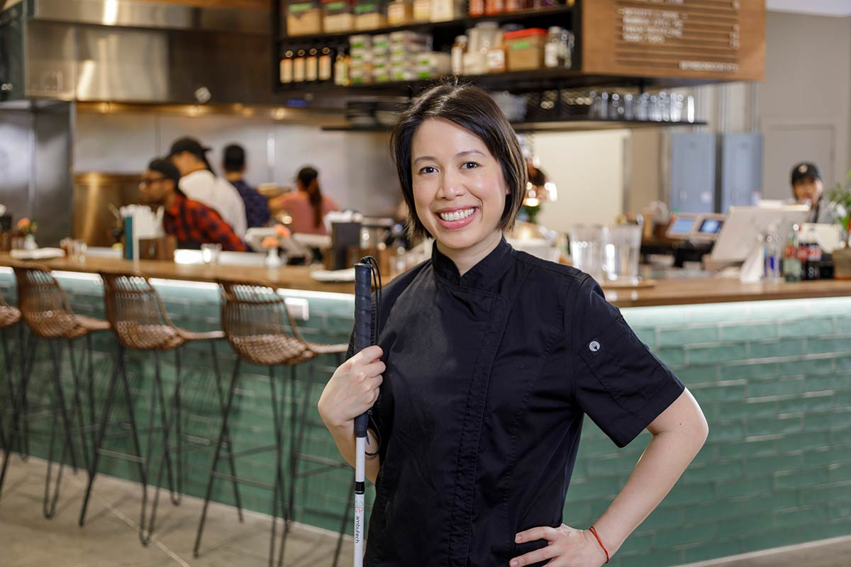 PHOTO: Christine Ha stands with her left hand on her hip and her other hand holding her white probing cane looking at the camera. Her dark brown hair hangs straight off her head, stopping just below her ears. She is smiling at the camera. Behind her is a counter with barstools and turquoise subway tiles that line the underside of the counter.