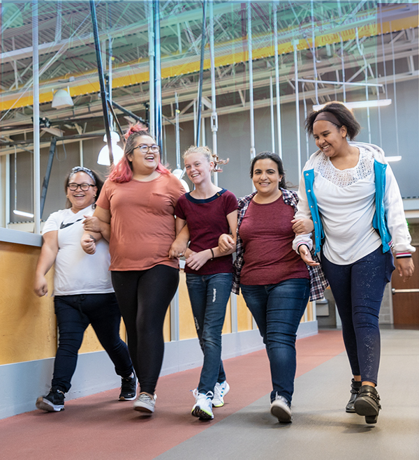 Five young women are walking on the Ability360 facility indoor track with their arms linked together, while laughing.