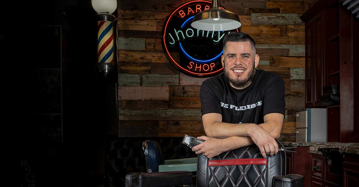 "PHOTO: A young hispanic man in his 20s sits behind an older-looking barber's chair with his arm crossed and leaning down on the back rest of the chair. He holds hair clippers in his left hand. He wears a black t-shirt that reads ""be flexible"" across the chest. His black hair is slicked to his right and cut short on the sides. He also has a full beard. Photo by Estefania Cavazos."