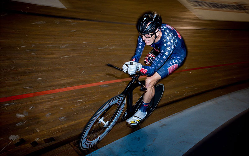 "PHOTO: Key racing a bike on an indoor track. Key wears a longsleeve blue bike suit that has white stars throughout and has the words ""USA"" on the outside of both his wrists and the outside of his left thigh. Key wears a black bike helmet and wears black-framed glasses.   Photo courtesy of Steve Cohen."