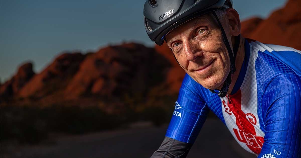 Todd Key leans over his bike and stares at the camera. Behind him sit the red Papago Park mountains. Key wears a matte black bike helmet, a Team USA bike short-sleeve shirt and black longsleeve shirt underneath. Key smiles tight-lipped smile. Photo by Loren Worthington.