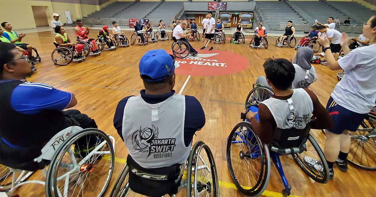 PHOTO: A group of about 30 people in sport wheelchairs in a circle listening to Coach Peter Hughes who is in the center of the circle in his own wheelchair. Photo by Mia Hanson.