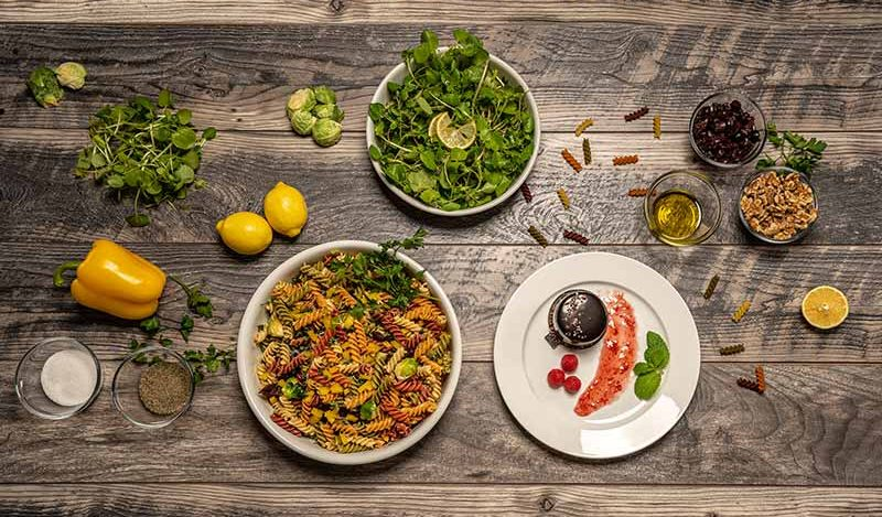 PHOTO: A spread of various ingredients and food laid out on a grey wood background. The staged photo shows glassware with salt, pepper, olives, walnuts, and olive oil in small glass dishes. Brussels Sprouts, bell peppers and lemons also lay out on the tile. In a larger white dish is multi-colored spiral pasta and mixed greens. On a white plate next to the large white dish is a display of a chocolate dessert a spread of a berry jam, three raspberrys and mint leaves. Photo by Estefania Cavazos.