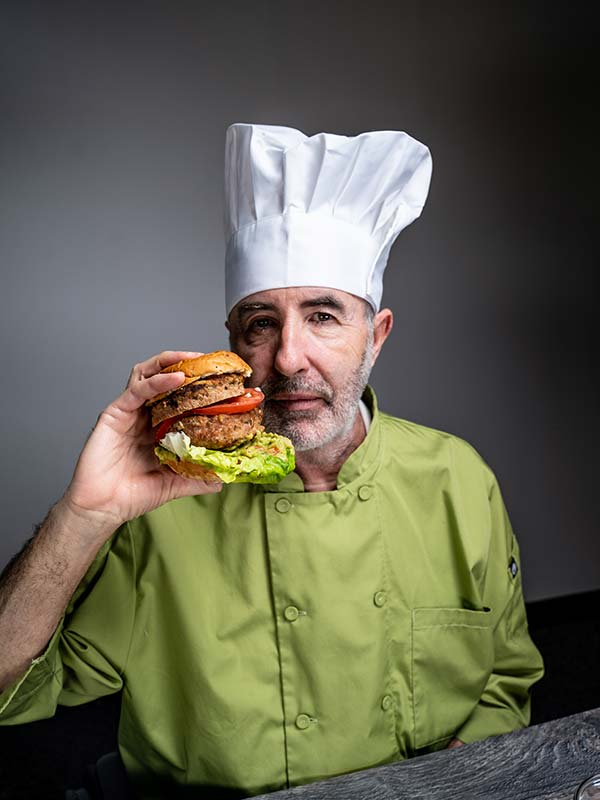 Chef Steve holds the turkey burger up to his mouth as if he were to take a bite of it.