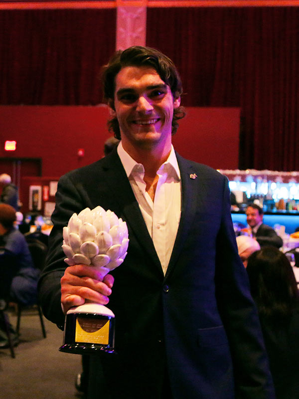 RJ Mitte smiles at the camera as he holds up his award.